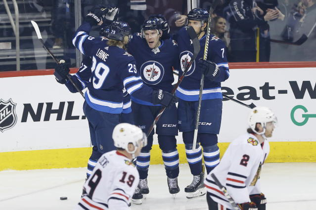 Winnipeg Jets left wing Nikolaj Ehlers (27), right wing Patrik Laine (29), center Paul Stastny (25) and defenseman Ben Chiarot (7) celebrate Stastny's goal against the Chicago Blackhawks during the first period of an NHL hockey game Thursday, March 15, 2018, in Winnipeg, Manitoba. (John Woods/The Canadian Press via AP)
