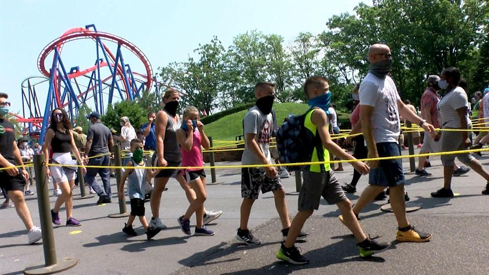 People wear masks as they arrive for Six Flags Great Adventure's opening day in Jackson Township, N.J., on July 3, 2020. The park had a delayed reopening for the summer season because of the spread of COVID-19.