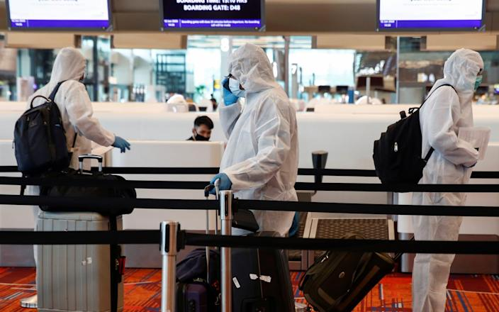 Seafarers who have spent the past months working onboard vessels arrive at Singapore's Changi Airport - Edgar Su/Reuters