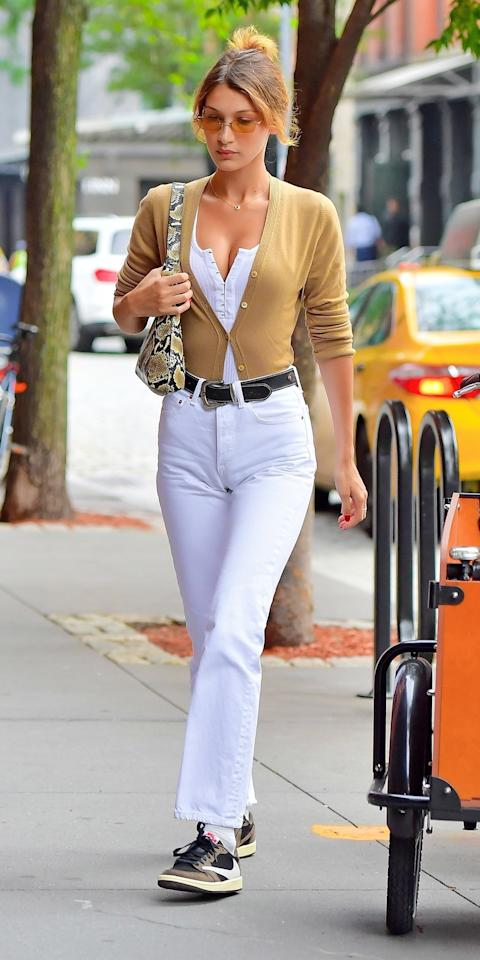 <p>Bella Hadid stepped out in New York City wearing a cardigan tucked into white jeans and styled with Travis Scott Jordan 1 sneakers, a python bag, and yellow tinted sunglasses.</p>