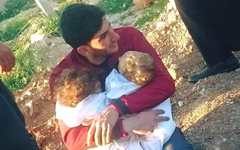 Abdulhamid Yussef cradles his twins Aya and Ahmad before they are buried in Idlib following a Sarin gas attack - Alaa al-Youssef