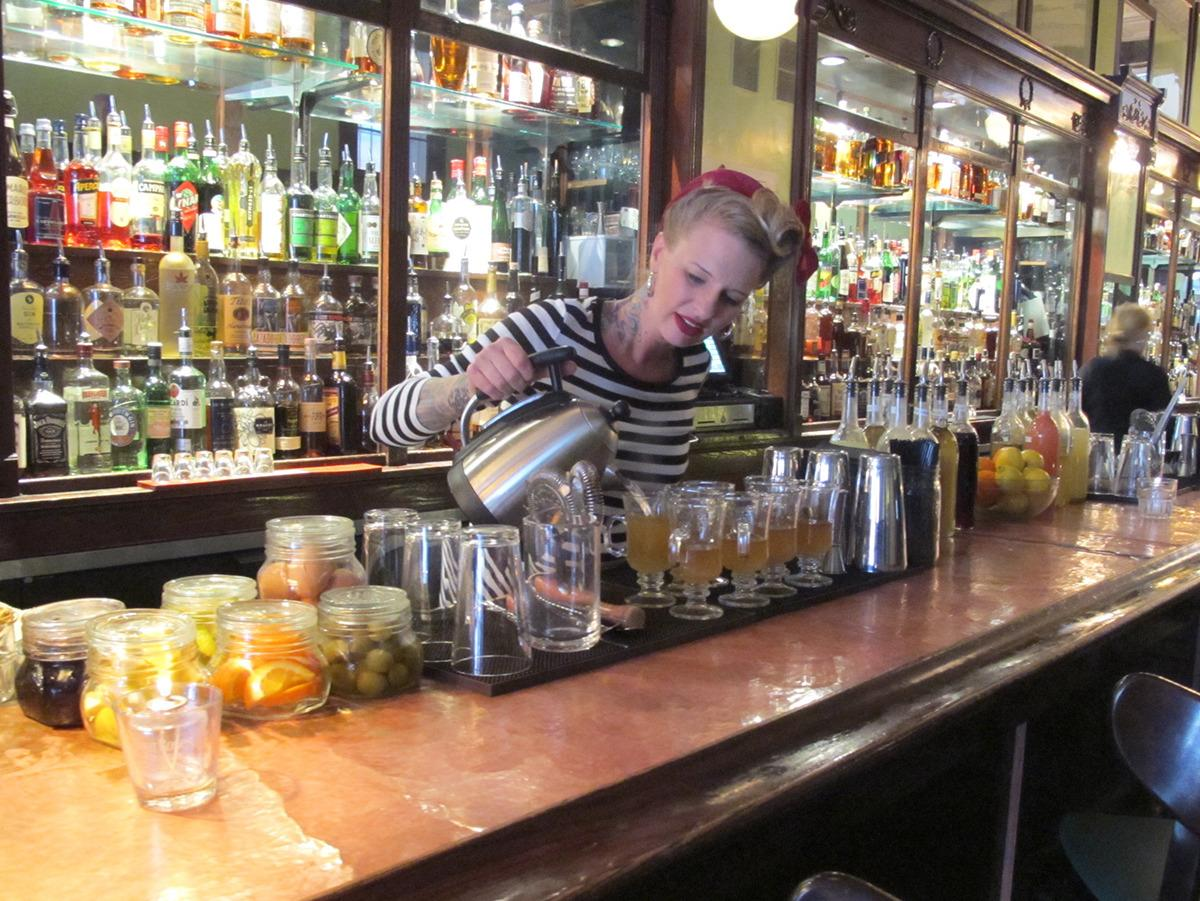 "<p>Molly Wellmann, behind several successful bars in town, pours hot toddies at <a href=""https://wellmannsbrands.com/japps1879/"">Japp's</a>, which is built in the site of a former wig and hair store, and keeps several historic elements of the old shop in tact. (<i>all photos: Gina Pace</i>)</p>"