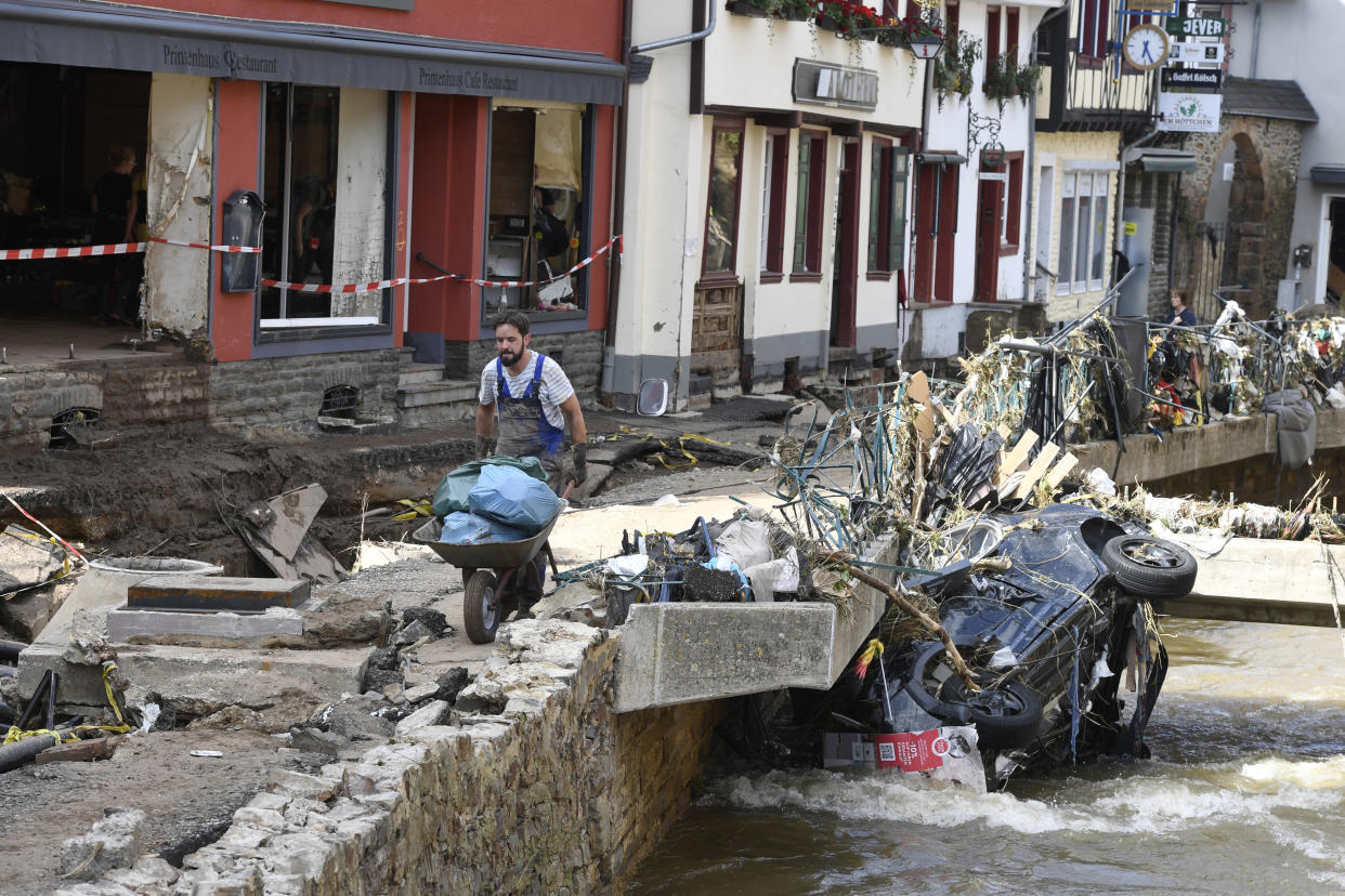 A man helps with the cleanup by carrying rubbish and debris after heavy rain and flooding along the Erft in Bad Münstereifel, Germany, Saturday, July 17, 2021. On the night of July 15, the Erft floods totally devastated the historic core of the city and flooded streets and shops. Gas, electricity and telephone lines were dangerously exposed. (Roberto Pfeil/dpa via AP)