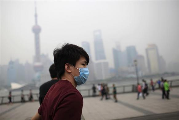 "A man wearing a mask walks along the Bund along the Huangpu River on a hazy day in Shanghai May 15, 2012. The U.S. consulate in Shanghai began posting hourly air quality readings for the city this week, with data showing ""very unhealthy"" conditions Tuesday afternoon. The consulate's classification reflects U.S. pollution standards, but operates on a different scale than the Shanghai Environmental Protection Bureau, which called conditions ""slightly polluted."""