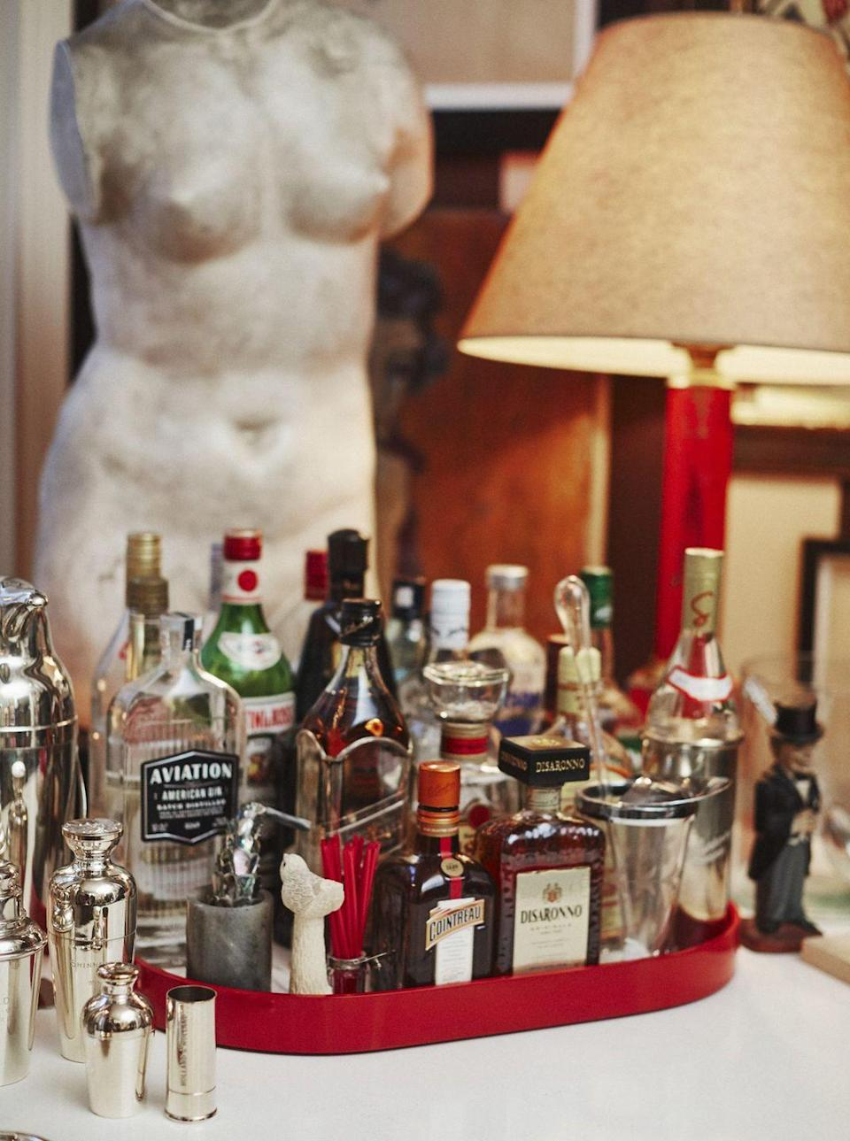 """<p>This artfully arranged bar scene by New York City designer <a href=""""http://milesredd.com"""" rel=""""nofollow noopener"""" target=""""_blank"""" data-ylk=""""slk:Miles Redd"""" class=""""link rapid-noclick-resp"""">Miles Redd</a> has us dreaming of cocktails by a crackling fire.</p><p>""""I've always been a big fan of drinks tables. I just love the way they look, and how they make a room feel. A bar just makes you comfortable. It's as if someone is telegraphing the message: <em>I am going to take care of you</em>,"""" he says. </p><p>Here, Redd uses a <a href=""""https://thelacquercompany.com/product/large-stacking-tray/"""" rel=""""nofollow noopener"""" target=""""_blank"""" data-ylk=""""slk:tray"""" class=""""link rapid-noclick-resp"""">tray</a> from his collection with <a href=""""https://thelacquercompany.com"""" rel=""""nofollow noopener"""" target=""""_blank"""" data-ylk=""""slk:the Lacquer Company"""" class=""""link rapid-noclick-resp"""">the Lacquer Company</a> to corral bottles, while a bust offers height and dimension to the scene. </p><p>""""As for what I put on them, the more elaborate the better, with all the usual suspects, of course. I do love the small bottles of mixers lined up like soldiers, and if you have the space, an array of snacks is always nice,"""" says Redd. </p><p>""""I love smoked almonds and various crisps, but do mind the packaging. No one wants to see a bag of Doritos. It's style over substance. If you do have to have a bag of chips, put them in small straw basket, like you see in a hotel mini bar.""""</p>"""