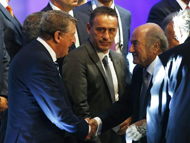 FIFA President Joseph Blatter, right, shakes hand with England manager Roy Hodgson, left, and Portugal head coach Paulo Bento looks on after the draw ceremony for the 2014 soccer World Cup in Costa do Sauipe near Salvador, Brazil, Friday, Dec. 6, 2013. (AP Photo/Victor R. Caivano)