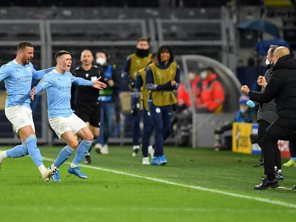 Phil Foden runs to celebrate with coach Pep Guardiola after scoring for City (Getty Images)