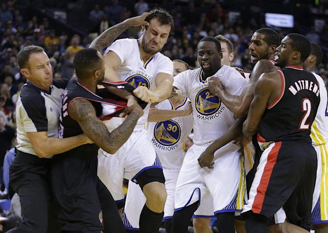 Portland Trail Blazers' Mo Williams, left, is restrained by a referee, left, as he fights with Golden State Warriors' Andrew Bogut (12) during the second half of an NBA basketball game Saturday, Nov. 23, 2013, in Oakland, Calif. Trail Blazers Wesley Matthews, Mo Williams, and Warriors' Draymond Green were ejected from the game. (AP Photo/Ben Margot)