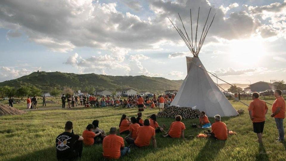 First Nations community members gather during a vigil in the recently discovered unmarked graveyard in a former catholic Indian residential school in Cowessess first nation community of Marieval, in Saskatchewan, Canada