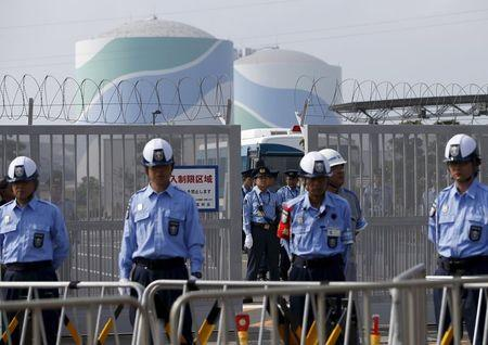 Police officers and security personnel stand guard at an entrance of Kyushu Electric Power's Sendai nuclear power station, during a protest demanding for the stop of the plant's restart, in Satsumasendai, Kagoshima prefecture, Japan August 9, 2015.    REUTERS/Issei Kato/Files