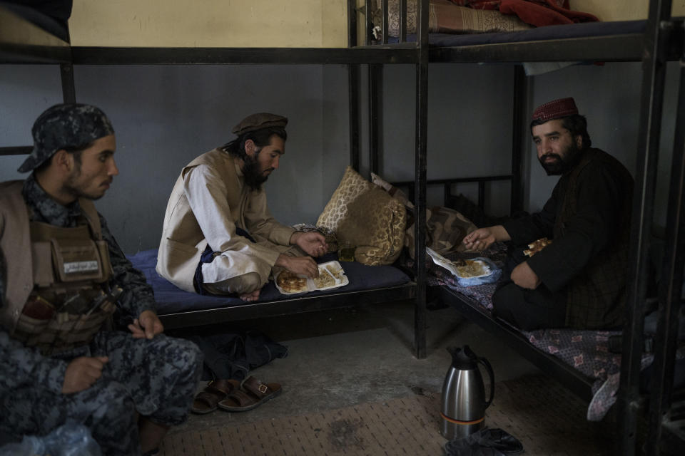 Taliban fighters eat lunch at a police station in Kabul, Afghanistan, Wednesday, Sept. 15, 2021. It is a symbol of the moment of transition they find themselves in: Once warriors embedded in Afghanistan's rugged mountains, now the Taliban are an urban police force. (AP Photo/Felipe Dana)