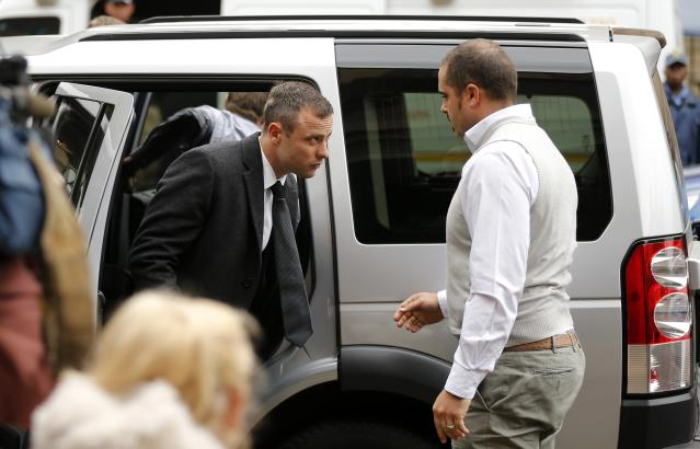 Olympic and Paralympic track star Oscar Pistorius (L) arrives ahead of his trial for the murder of his girlfriend Reeva Steenkamp at the North Gauteng High Court in Pretoria, April 14, 2014. Pistorius is on trial for murdering Steenkamp at his suburban Pretoria home on Valentine's Day last year. He says he mistook her for an intruder. REUTERS/Siphiwe Sibeko (SOUTH AFRICA - Tags: SPORT ATHLETICS CRIME LAW)