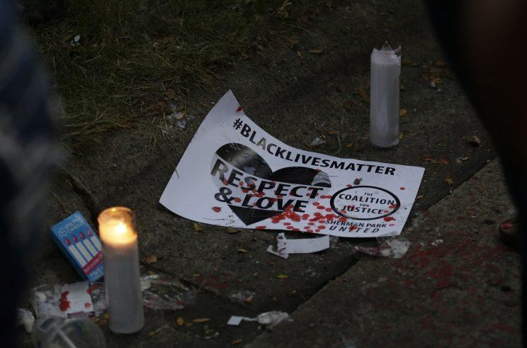 A sign and candles were left at the location where Sylville Smith was shot and killed by a Milwaukee police officer. (Photo: Jeffrey Phelps/AP)