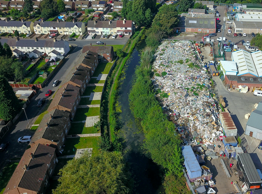 The towering pile of waste has now grown higher than nearby trees and houses. (SWNS)