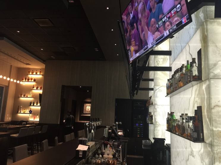 At a mostly empty The Woods, the restaurant owned by Tiger Woods, TVs were tuned to replays of the NBA playoffs. (Yahoo Sports)