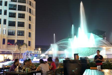 Locals enjoy the evening in one of the nearby restaurants around the Nam Phou fountain in Vientiane