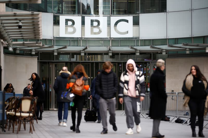 Pedestrians walk past a BBC logo at Broadcasting House, as the corporation announced it will cut around 450 jobs from its news division, in London
