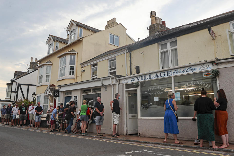 People queue outside the fish and chip shop in Shaldon, Devon, England, Friday July 23, 2021. Visiting the fishing village of Shaldon a small cluster of mainly Georgian houses and shops at the mouth of the River Teign, is like stepping back into a bygone era. It features simple pleasures that hark back to analog, unplugged summer days: a book and a picnic blanket, a bucket and spade, fish and chips. (AP Photo/Tony Hicks)