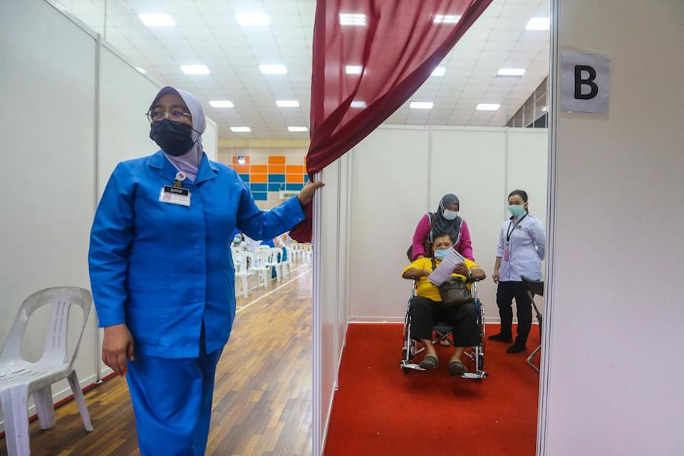 A senior citizen receives their Pfizer-BioNTech Covid-19 vaccine during the National Covid-19 Immunisation Programme at Dewan Kompleks Sukan Pandamaran in Klang May 7, 2021. — Picture by Yusof Mat Isa