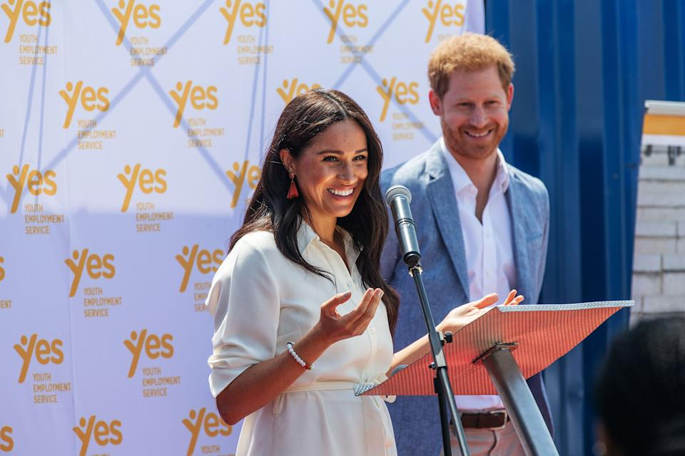 """Meghan, Duchess of Sussex(L), is watched by Britain's Prince Harry, Duke of Sussex(R) as  she delivers a speech at the Youth Employment Services Hub in Tembisa township, Johannesburg, on October 2, 2019. - Meghan Markle is suing Britain's Mail On Sunday newspaper over the publication of a private letter, her husband Prince Harry has said, warning they had been forced to take action against """"relentless propaganda"""". (Photo by Michele Spatari / AFP) (Photo by MICHELE SPATARI/AFP via Getty Images)"""