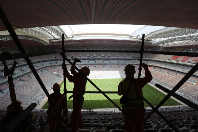 Workers remove scaffolding at Al Bayt Stadium in Al Khor, Qatar. (AP Photo/Kamran Jebreili)
