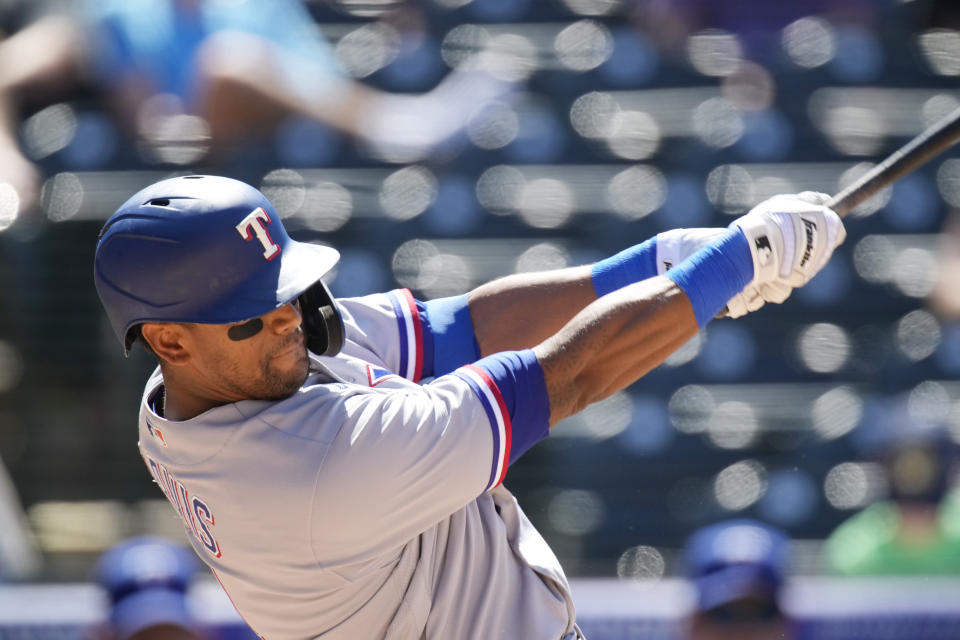 Texas Rangers' Khris Davis connects for a two-run home run off Colorado Rockies relief pitcher Jordan Sheffield in the seventh inning of a baseball game Thursday, June 3, 2021, in Denver. (AP Photo/David Zalubowski)