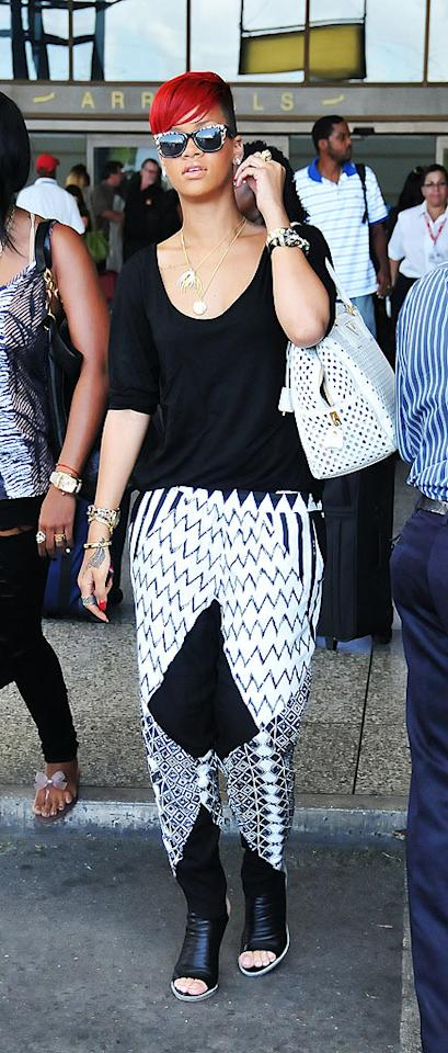 "Rihanna paired scary harem pants and frightening bright red locks atop a shaved head as she arrived in her native Barbados on Wednesday. Yikes! Islandpaps/<a href=""http://www.splashnewsonline.com"" target=""new"">Splash News</a> - June 16, 2010"