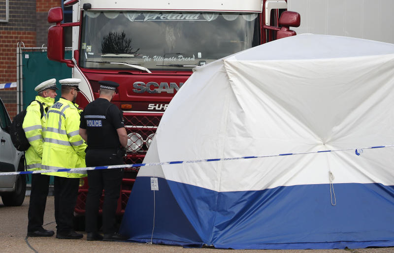 Police officers attend the scene after a truck was found to contain a large number of dead bodies, in Thurrock, South England, early Wednesday Oct. 23, 2019. Police in southeastern England said that 39 people were found dead Wednesday inside a truck container believed to have come from Bulgaria. (AP Photo/Alastair Grant)