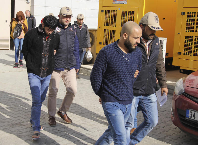 Turkish police officers escort people suspected of being Islamic group militants, outside a court in the Black sea region city of Samsun, Turkey, Thursday, Nov. 9, 2017. Police on Thursday detained at least 111 suspected Islamic State group militants in a sweep in the capital, Ankara, Police on Thursday detained at least 111 suspected Islamic State group militants in raids in the capital, Ankara, Turkey's state-run news agency reported.Authorities had detention warrants for a total of 245 IS suspects, Anadolu Agency said, suggesting that operations for the other alleged militants were continuing. (Muhammer Ay/IHA Photos via AP)