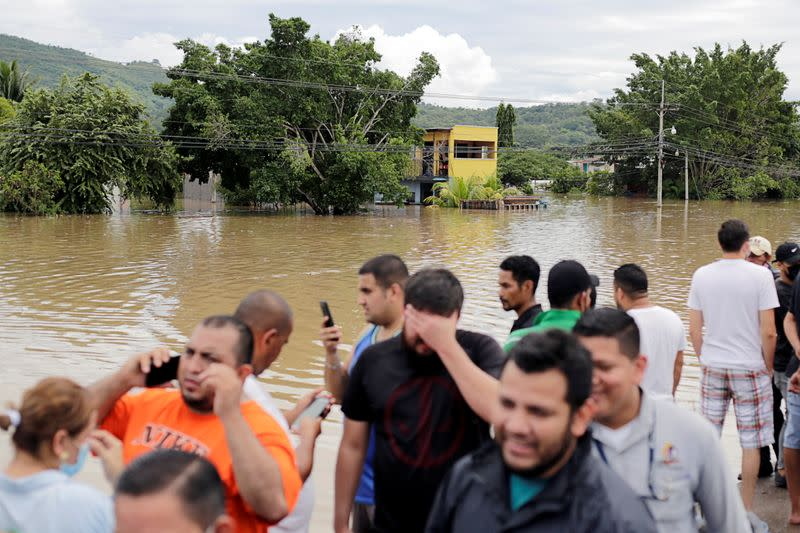 People react while standing outside a flooded neighbourhood during the passage of Storm Eta, in Pimienta