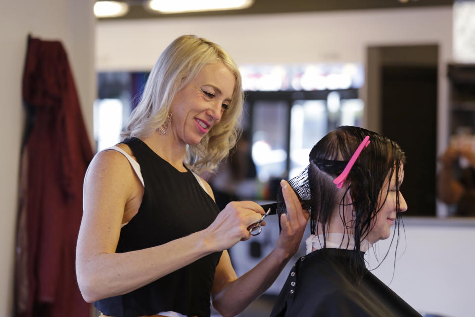 """In this photo taken Monday, Nov. 4, 2019, hair stylist Marisa """"Malibu"""" Anthony works on a customer's hair in a shop in Seattle. (AP Photo/Elaine Thompson)"""