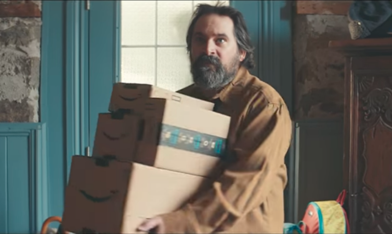 The ad features a dad carrying a bunch of Amazon parcels. Photo: Youtube