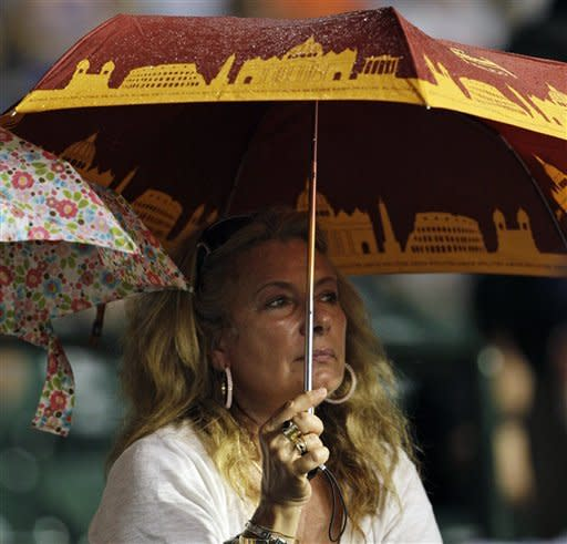 A fan holds an umbrella as she watches the Miami Marlins play against the Chicago Cubs during the eighth inning of a baseball game in Chicago, Wednesday, July 18, 2012. (AP Photo/Nam Y. Huh)