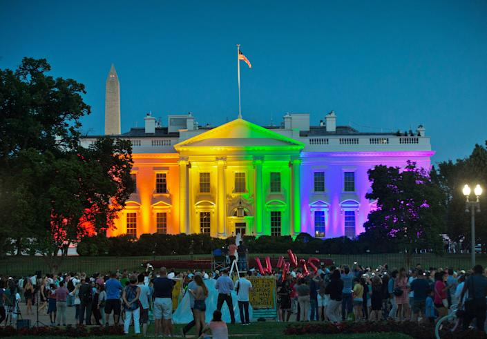 In this Friday, June 26, 2015 file photo, people gather in Washington's Lafayette Park to see the White House illuminated with rainbow colors to mark the U.S. Supreme Court's ruling to legalize same-sex marriage.
