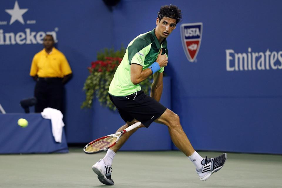 Thomaz Bellucci, of Brazil, hits a shot between his legs to Stan Wawrinka, of Switzerland, during the second round of the U.S. Open tennis tournament Wednesday, Aug. 27, 2014, in New York. (AP Photo/Jason DeCrow)