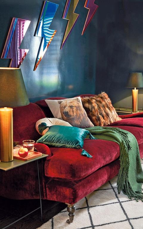 Cushions are piled up on the deep-red velvet sofa, custom-designed by Joanna Plant (joannaplantinteriors.com). The lightning-bolt mirrors are by Bride & Wolfe (antipodream.co.uk) - Credit: joannaplantinteriors.com; antipodream.co.uk