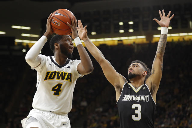 Iowa guard Isaiah Moss (4) drives to the basket as Bryant guard Byron Hawkins (3) defends during the first half of an NCAA college basketball game Saturday, Dec. 29, 2018, in Iowa City, Iowa.(AP Photo/Charlie Neibergall)