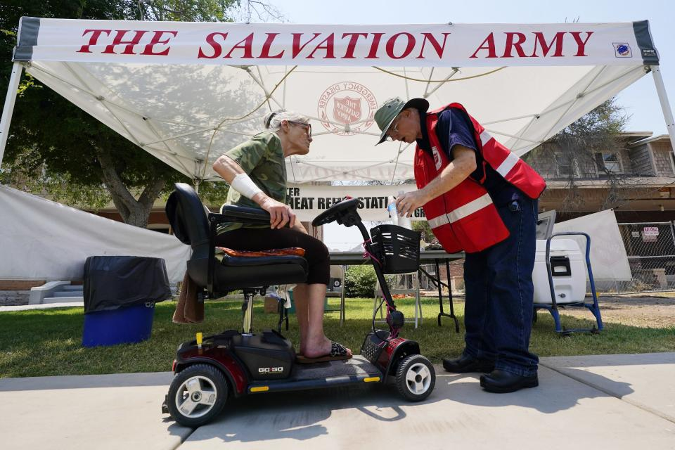Salvation Army hydration station volunteer Paul Spiri, right, hands out water during a heatwave as temperatures hit 115-degrees, Tuesday, June 15, 2021, in Phoenix. (AP Photo/Ross D. Franklin)