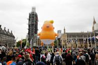 A giant balloon depicting US President Donald Trump as an orange baby floats above anti-Trump demonstrators in Parliament Square outside the Houses of Parliament in London on June 4 (TOLGA AKMEN/AFP/Getty Images)