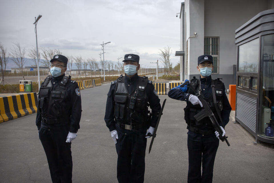 Police officers stand at the outer entrance of the Urumqi No. 3 Detention Center in Dabancheng in western China's Xinjiang Uyghur Autonomous Region on April 23, 2021. Urumqi No. 3, China's largest detention center, is twice the size of Vatican City and has room for at least 10,000 inmates. (AP Photo/Mark Schiefelbein)