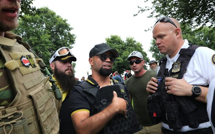Tarrio, chairman of the alt-right group Proud Boys, speaks with a police officer during the End Domestic Terrorism rally in August 2019