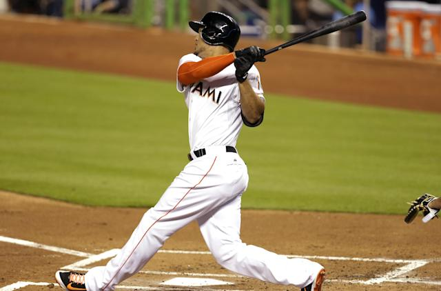 Miami Marlins' Giancarlo Stanton follows through on a three-run home run during the first inning of the MLB National League baseball game against the Washington Nationals, Tuesday, April 15, 2014, in Miami. (AP Photo/Lynne Sladky)