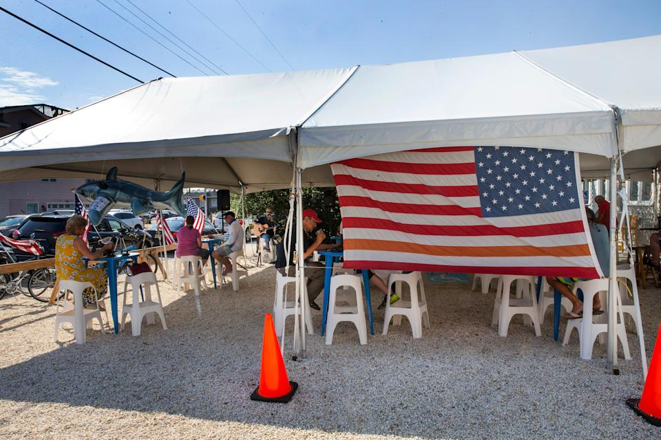 Customers eat and drink outside under tents at the Surf City Hotel in Surf City.