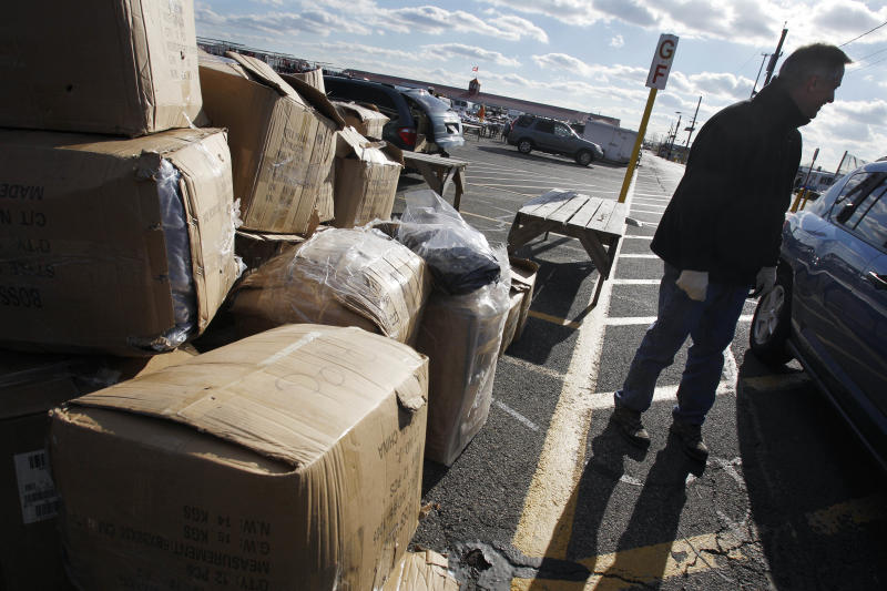 In this Dec. 9, 2010 photo, New Jersey State Police Lt. Michael E. McDonnell stands near boxes of fake name-brand clothing. in Columbus, N.J., that police seized from a vendor at the Columbus Flea Market. (AP Photo/Mel Evans)