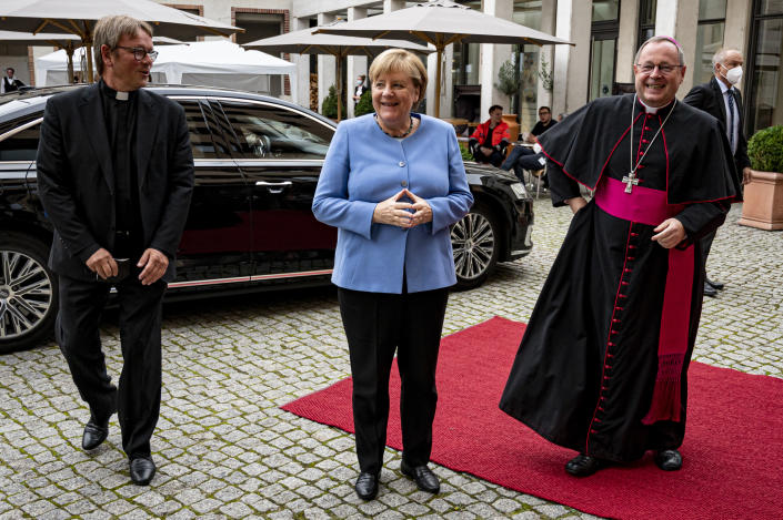 German Chancellor Angela Merkel is greeted by Georg Batzing, right, President of the German Bishops' Conference, and Karl Justen, Head of the Commissariat of the German Bishops, before the St Michael 2021 Annual Reception of the German Bishops' Conference in Berlin, Monday Sept. 27, 2021. (Fabian Sommer/dpa via AP)