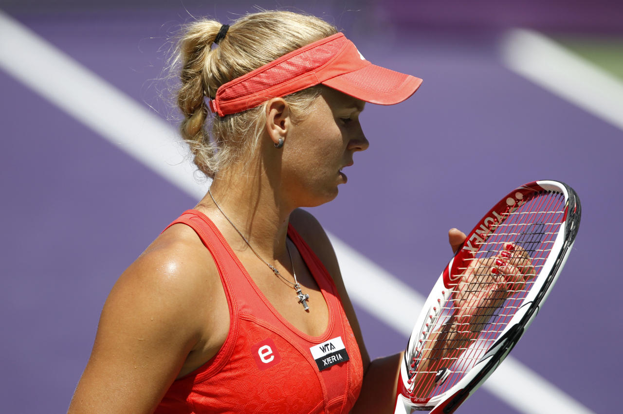 Caroline Wozniacki of Denmark, adjusts her racket during a match against Maria Sharapova of Russia, during the Sony Ericsson tennis tournament, Thursday, March 29, 2012, in Key Biscayne, Fla. (AP Photo/Lynne Sladky)