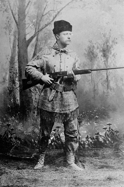 """FILE - In this undated photo provided by Harvard University Press, President Theodore Roosevelt, posing as an """"outdoorsman,"""" points his rifle during a studio photo session. AP Photo/Harvard University Press)"""