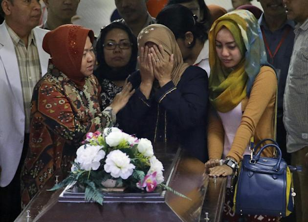 """A relative weeps during the handover of the body of Hayati Lutfiah, one of the victims of AirAsia Flight 8501, to her family at the police hospital in Surabaya, East Java, Indonesia, Thursday, Jan. 1, 2015. Searchers were racing """"against time and weather"""" Thursday to recover the dead from the crash, with a window of good conditions slammed shut by another onslaught of wind and heavy rain. (AP Photo/Dita Alangkara)"""