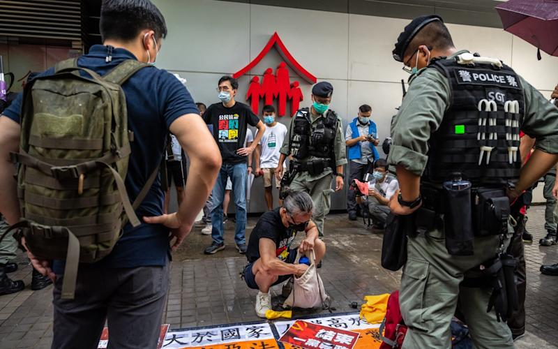 Riot police searching pro-democracy protesters in Hong Kong on Wednesday - GETTY IMAGES