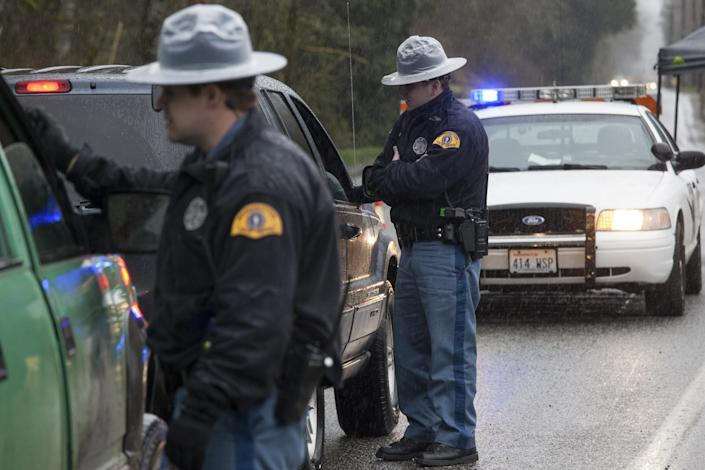 Washington State Patrol troopers stop vehicles at a road block on a local highway: David Ryder/Getty Images